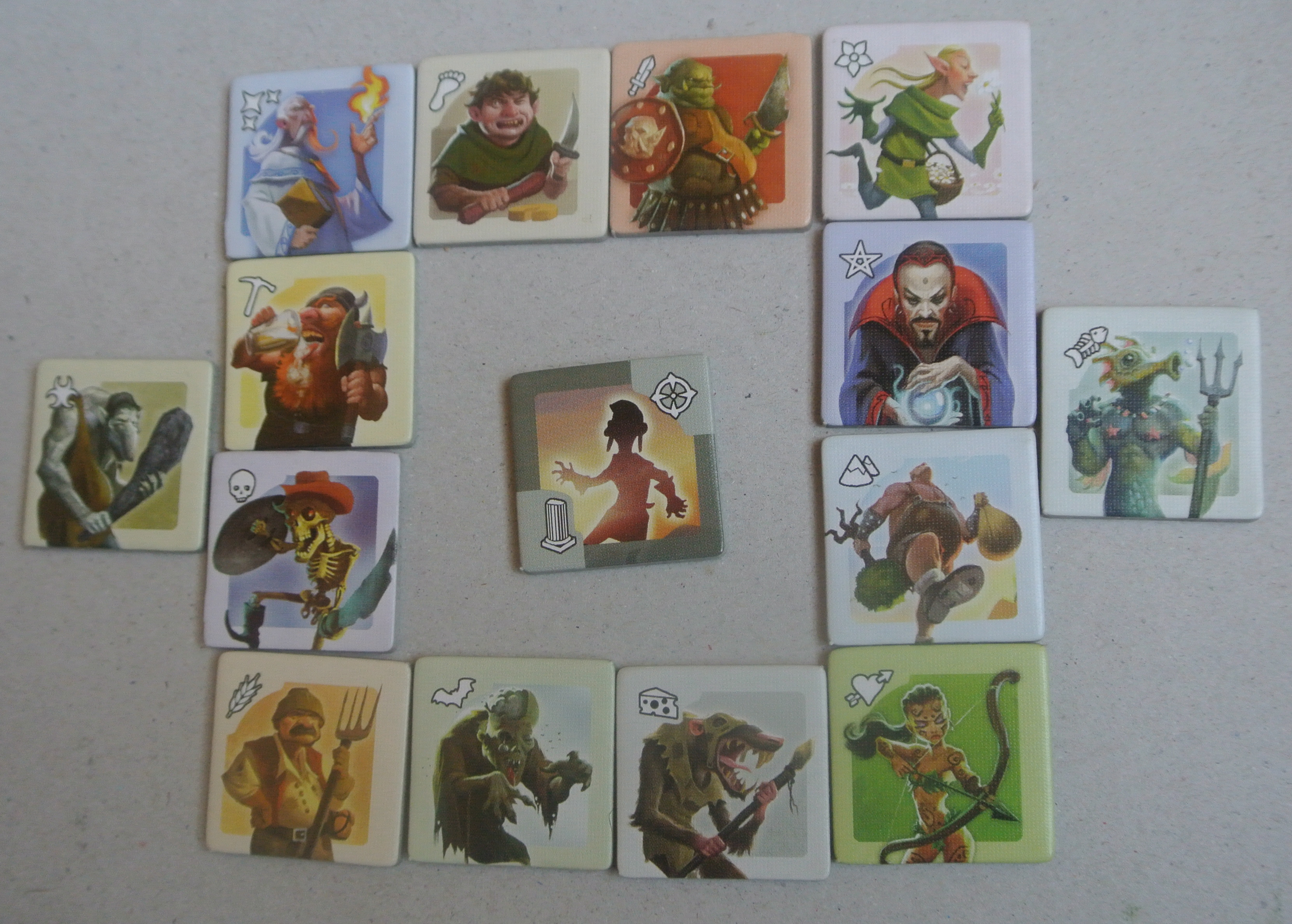 Race tokens from Small World, with the Lost Tribes in the center. Image used with permission of the author, and reproduced for purposes of critique.