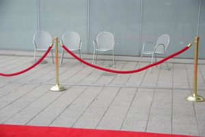 This is an image of velvet ropes in front of a table and chairs